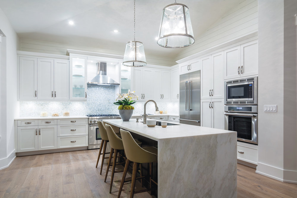 In the expanded kitchen, the Honed Mystery White marble island is the focal point and creates a great prep space. The custom backsplash and shiplap details create a special area of the home.