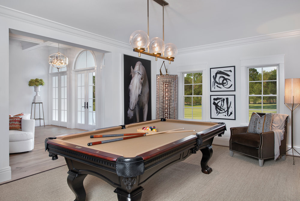 """I wanted to create a distinctly masculine area in this house and I think this room turned out to be a wonderful space with a global feel,"" says Williams of the billiards room. Roman shades, the animal skin rug, and antler accents add exotic touches to the classic pool table and leather sofa. The artwork is from August's Wendover Collection."