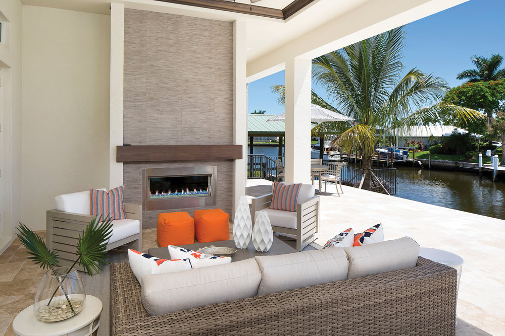 The lanai offers multiple seating and entertaining areas. The main living space is a fun mix of vibrant orange and resort-style seating options. The fireplace with vibrant blue glass and the feature wall create the perfect outdoor focal point. Beyond, a dining table offers al fresco dining options on the water. The lanai was designed to flow between the main seating area, the grill station, the dining space, and the pool. This creates separation so nothing feels crowded while also allowing for a cohesive entertaining environment.