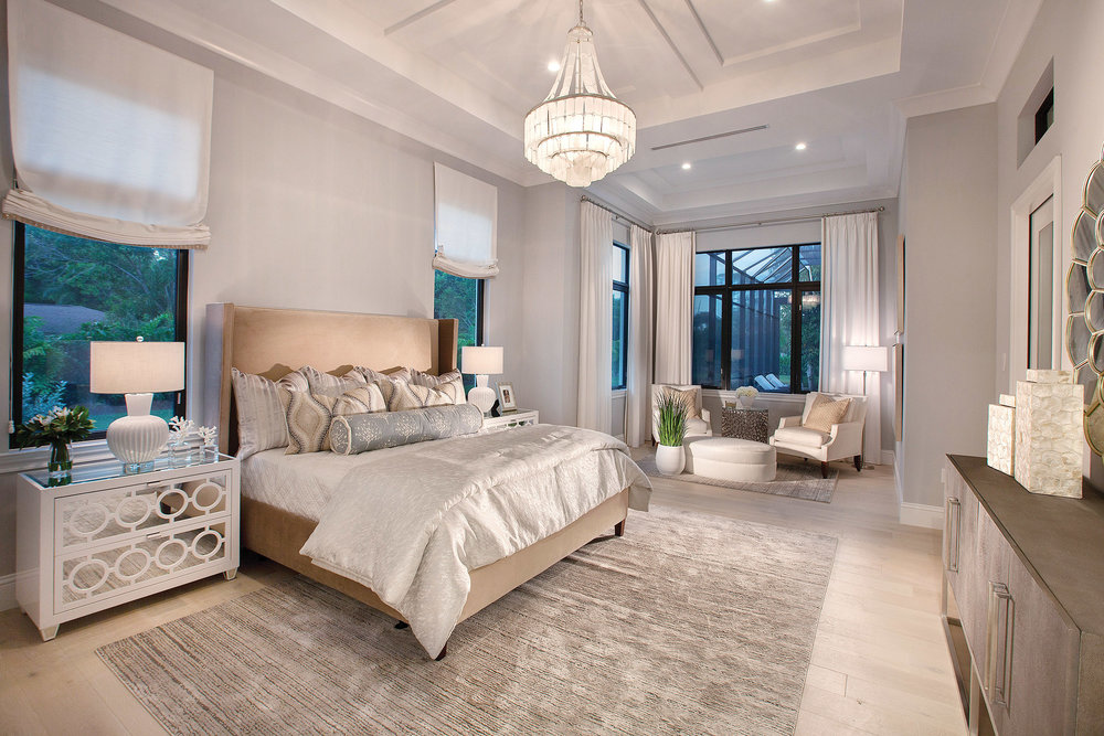 The spacious master suite offers a private sitting area which opens to the outdoors. Coffered ceiling details, the warm wood flooring, neutral colors, and soft textures provide a luxurious feel and serene setting.