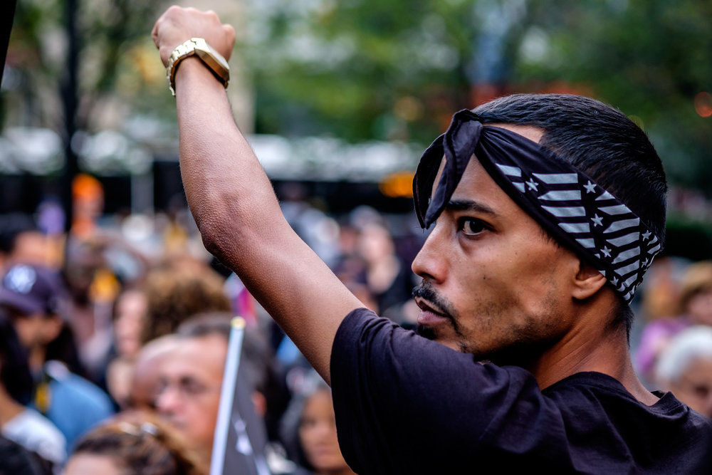 A man with a bandana raises his fist to show support for Puerto Rico at the 1 year anniversary of Hurricane Maria Rally at Union Square in New York City.