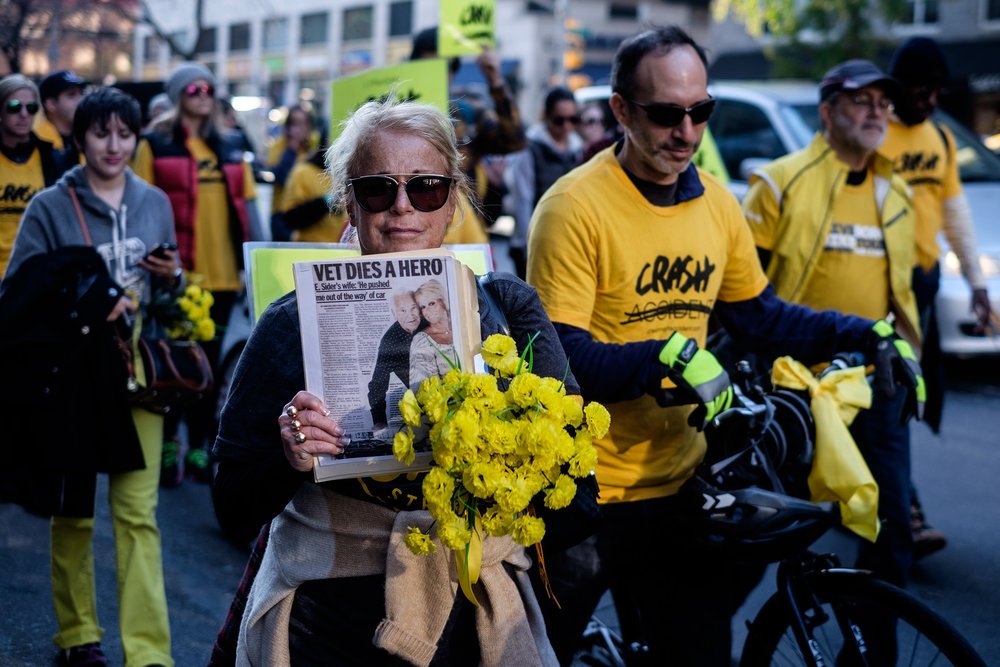 A woman with flowers holds up an article relating to the death of an elderly man struck by a motor vehicle during a rally for increased pedestrian safety in New York City.