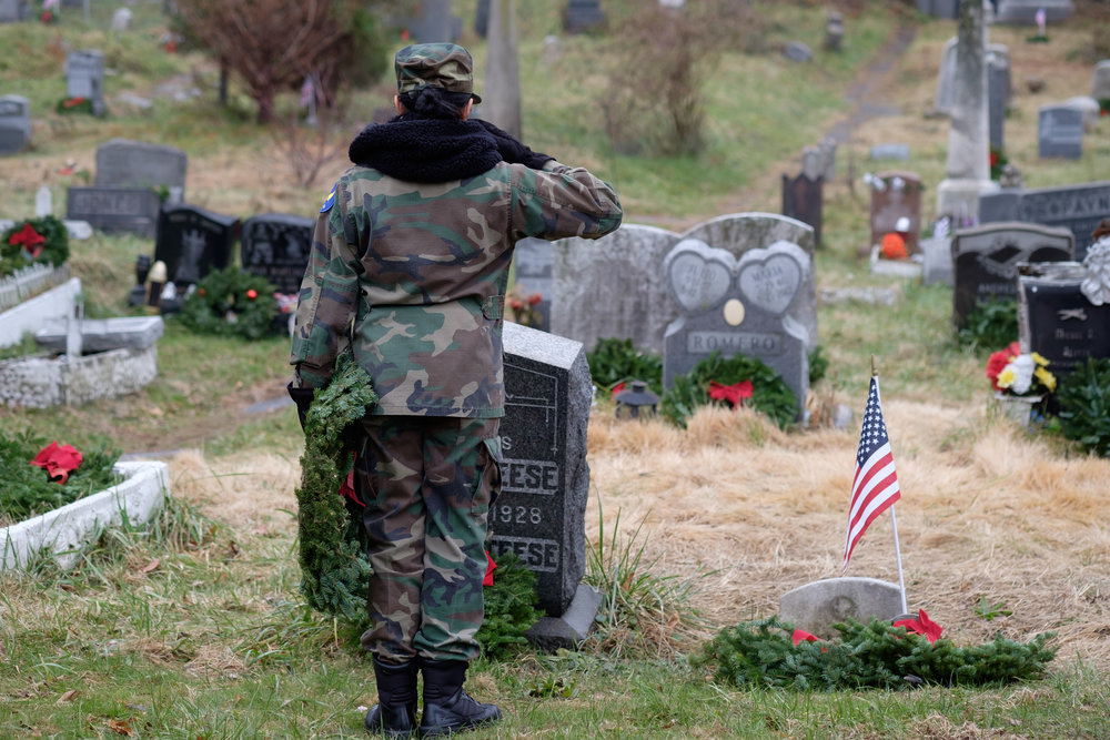 A member of the Civil Air Patrol salutes a fallen soldier in Harsimus Cemetary in Jersey City, NJ.
