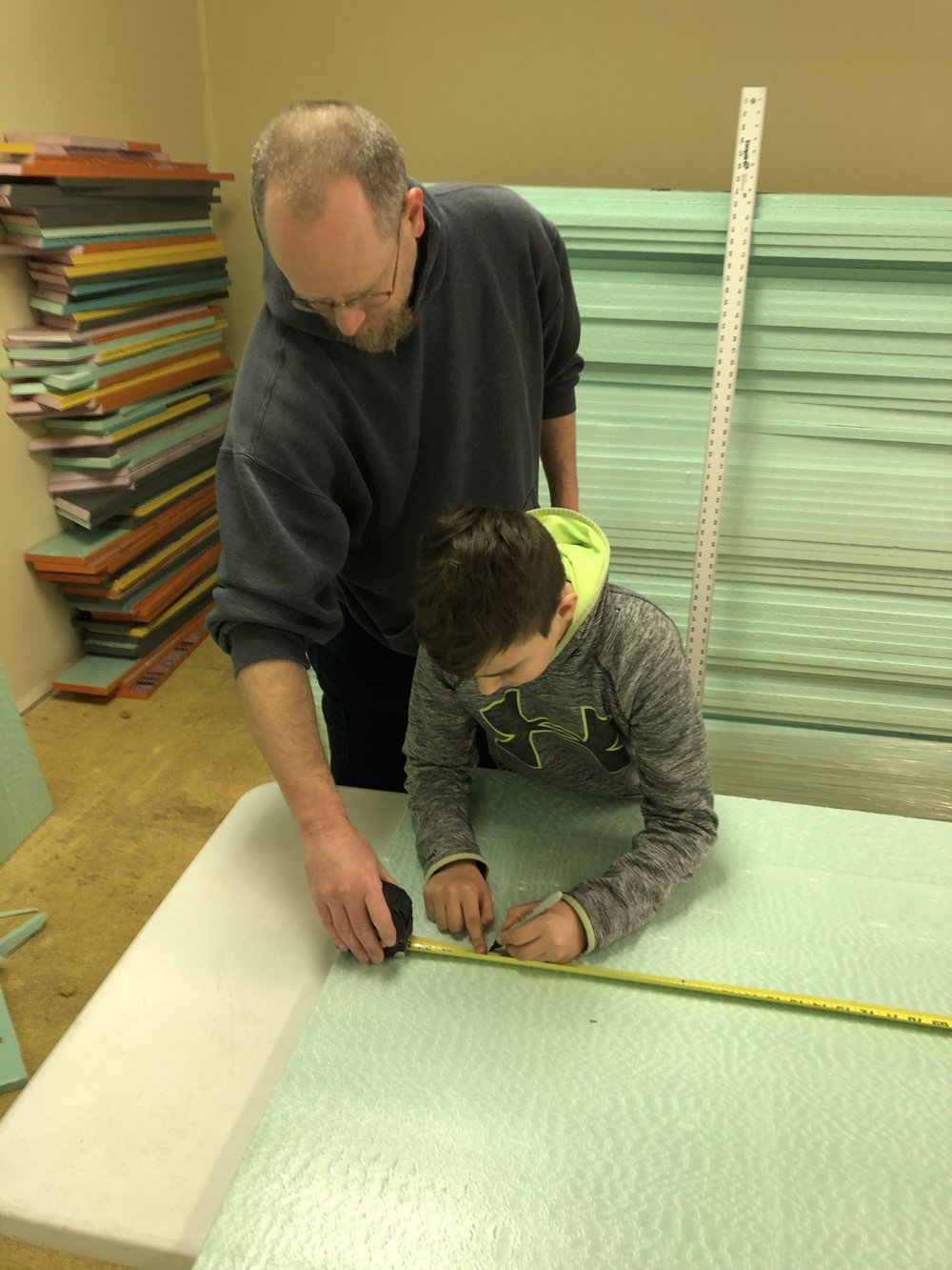 A father and son help cut insulation for one of the shelters