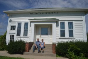 Jan and her husband Rob in front of their 1928 schoolhouse, which they converted into their home (photo credit NRCS)