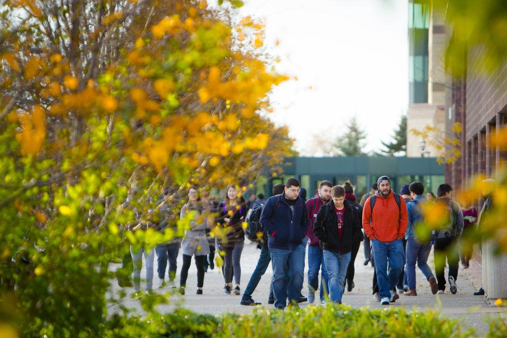 University at Buffalo students walking on campus during fall semester.