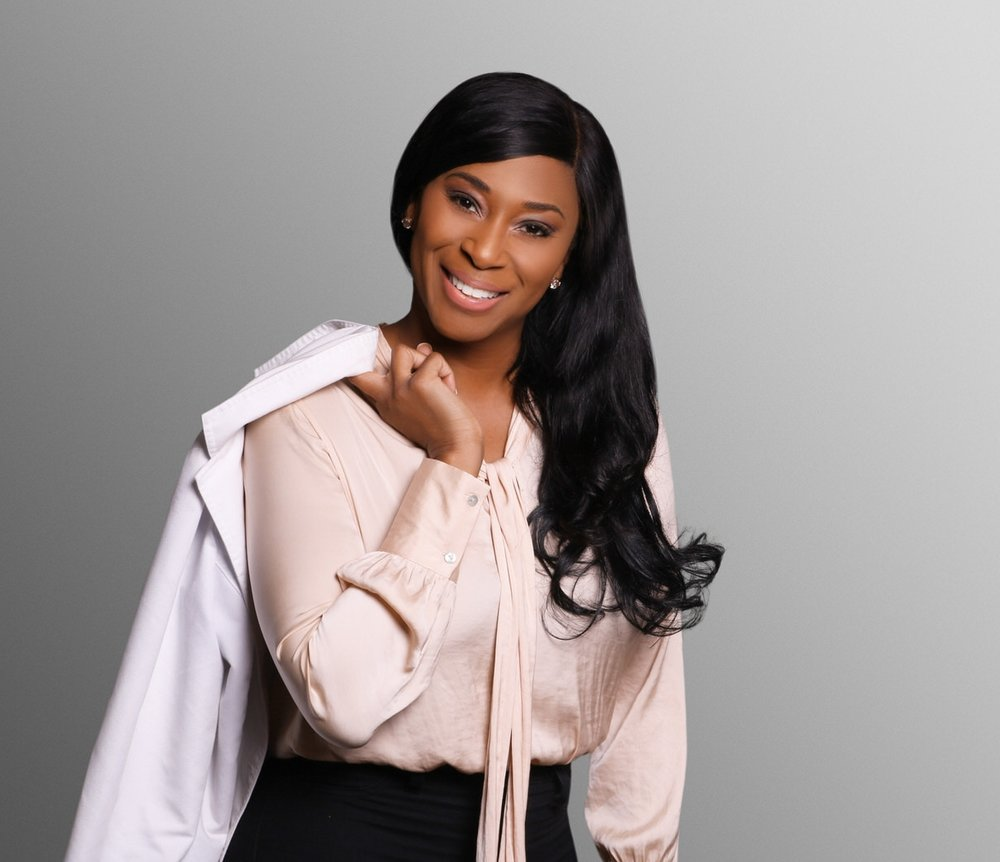 African-American woman in beige blouse  and black pants, holding white lab coat, gray background.jpg