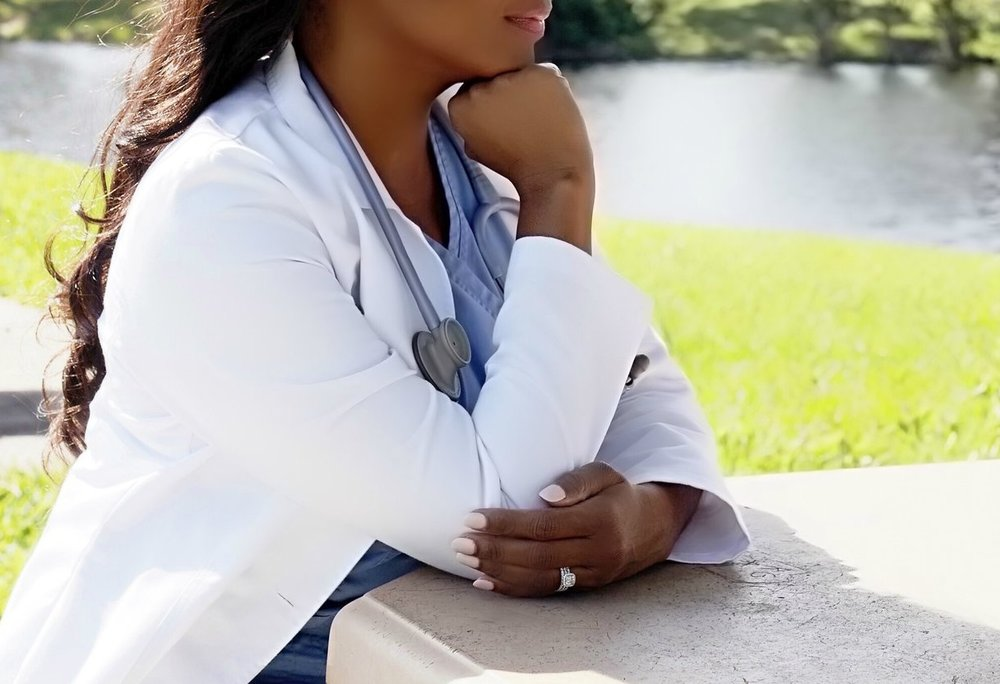 African American Woman Wearing a White Lab Coat and Blue scrubs with a stethoscope.jpg