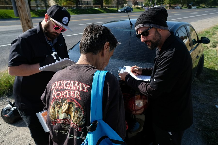 (Francisco Kjolseth | The Salt Lake Tribune) Alex Larson, left, and Patrick Rezac, right, Executive Director of One Voice Recovery, check in with Ivan Vasquez, 58, who is homeless and a heroin user in West Salt Lake recently. In an effort to curb the incidents of Hepatitis, HIV and STD's, Rezac's grass roots team hands out disease prevention kits and provides a needle exchange program.