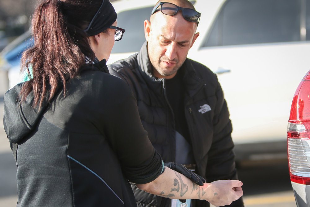 Patric Rezac examines a clients arm after she reported feeling numbness and pain in Salt Lake City on Thursday, Dec. 14, 2017. Patric is the founder and director of One Voice Recovery Inc., a nonprofit needle exchange organization that works in conjunction with the Salt Lake County Health Department to provide care for homeless and in need Utah residents.