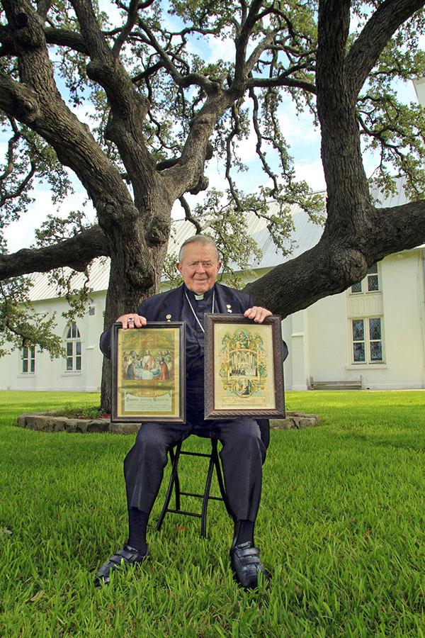 Our Founder, Bishop John W. Yanta, under the same oak tree where, in 1854, the Polish settlers celebrated their first Mass in Texas at midnight on Christmas Eve. He is holding the wedding and baptism certificates from his ancestors who received Sacraments at Panna Maria. -