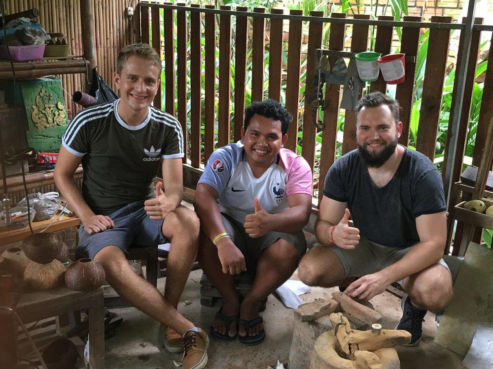 Soth, Siem Reap - Kambodscha - Suasdey! Ich bin Soth. Ursprünglich komme ich aus einem kleinen Dorf in der Nähe von Siem Reap. Besonders die Dorfbevölkerung hat es schwer in Kambodscha. 53 % der Bevölkerung in unserer Provinz um Siem Reap leben in Armut. Drei Tage die Woche arbeite ich an Handwerkskunst aus Kokosnüssen, die ich gemeinsam mit Bamboo Shoots auf dem lokalen Handwerksmarkt verkaufe. Billige Produkte aus Nachbarländern machen es schwerer und schwerer die Kunst zu verkaufen. Deshalb helfe ich an den restlichen zwei Tagen in den Schulen aus. Meinn Handwerk habe ich von Älteren aus dem Dorf gelernt.Damit führt Soth eine lange Tradition fort. Als wir Bamboo Shoots vor Ort besuchten konnten wir uns persönlich von seinem Können und gewissenhaftem Arbeiten überzeugen. Während wir uns nicht besonders geschickt mit dem Werkzeug anstellten, sitzt bei Soth jeder Handgriff. Wir hoffen ihm mit unserer Arbeit in Zukunft einen stabilen Arbeitsplatz zu sichern.Hier erfahrt ihr mehr zur NGO: https://www.facebook.com/bambooshoots.ev/