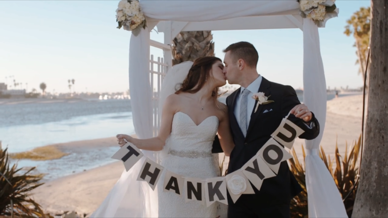 "Matt & Lindsay holding a ""Thank You"" banner while kissing."