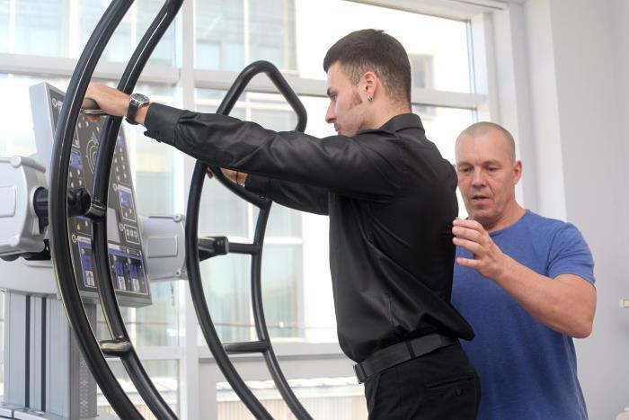 Сертифицированный тренер контролирует занятие на тренажере HUBER