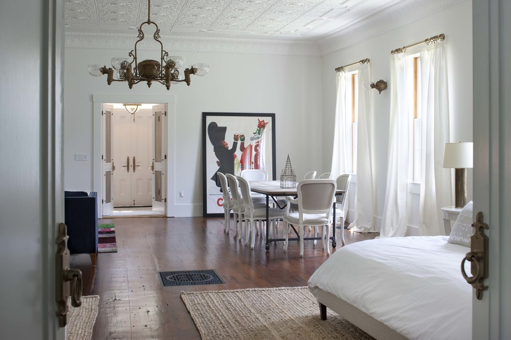 Bedroom with small table and chandelier.