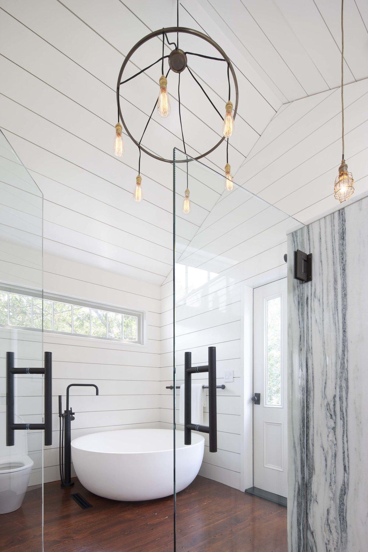 Modern bathroom with bathtub and decorative lighting.