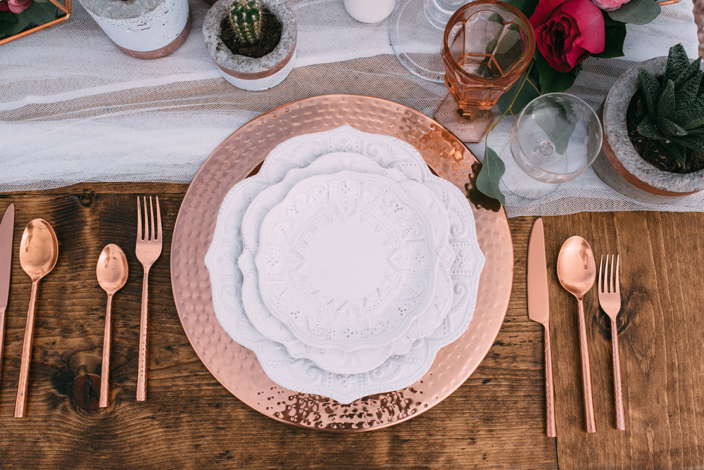 copper and white place setting with copper silverware for a wedding