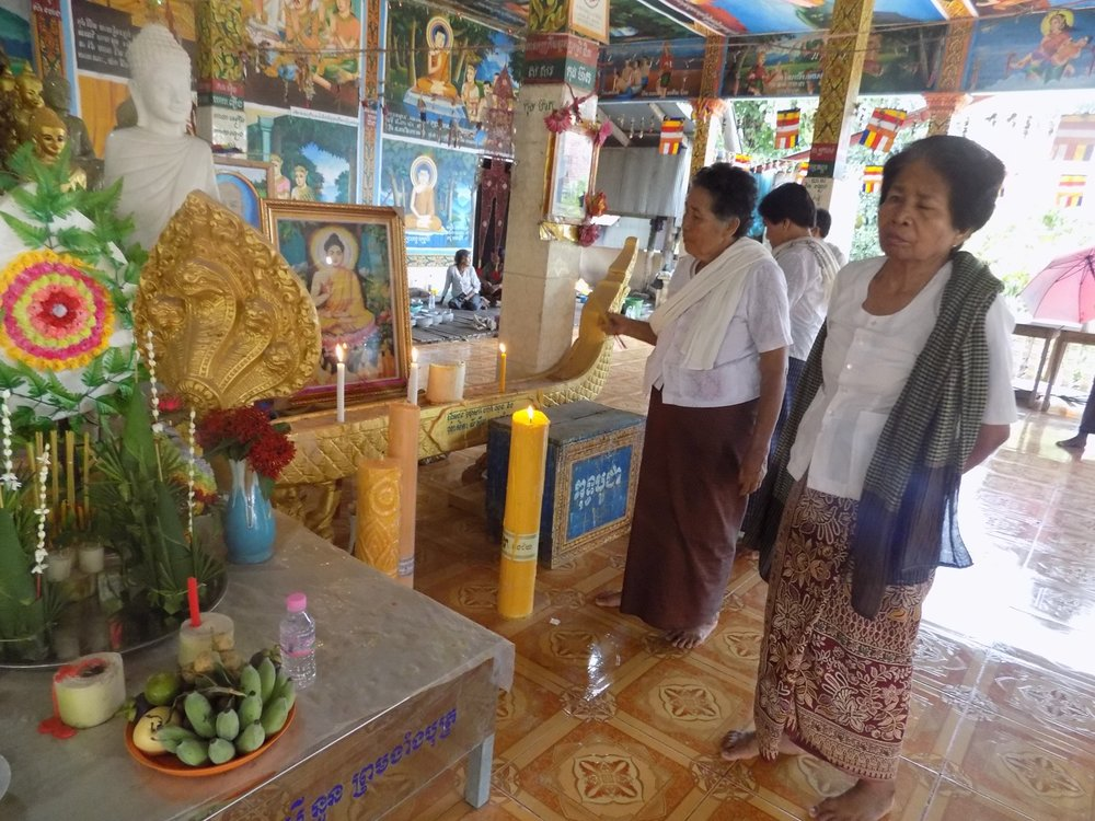 Women of the village visit the shrine to Buddha.