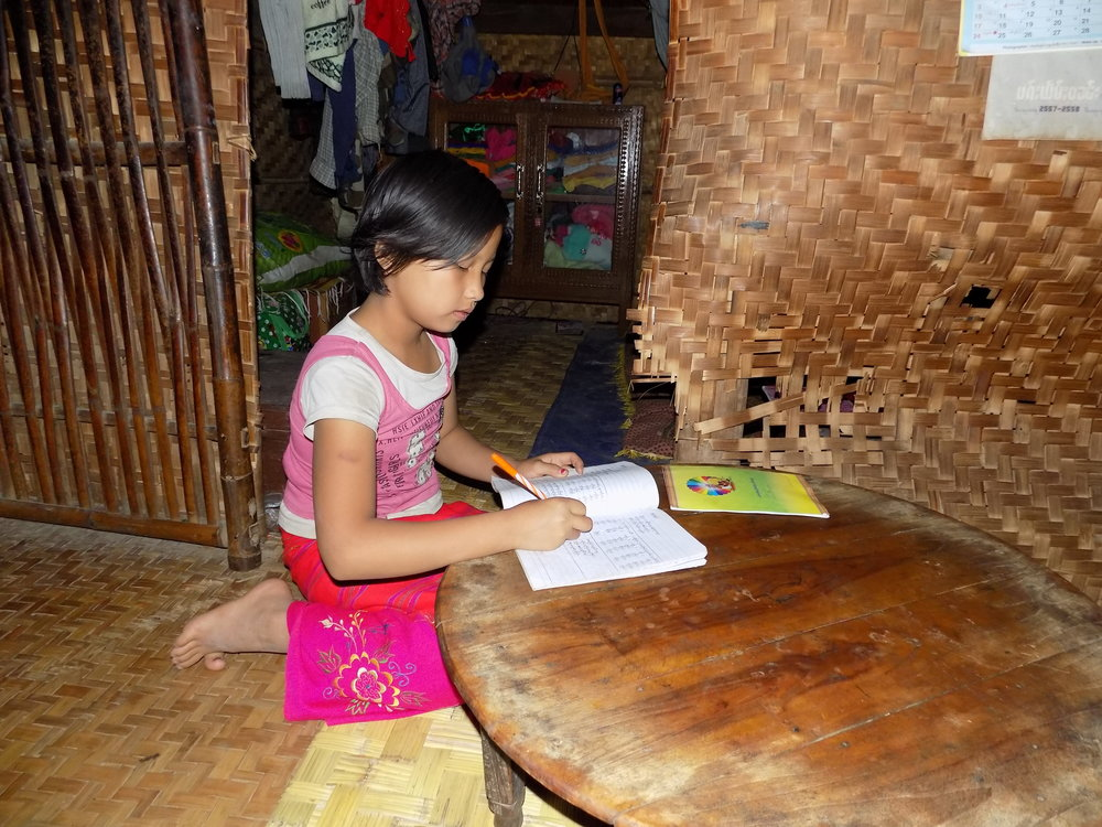 Nung Lao Ngun does her homework after she finishes dinner.