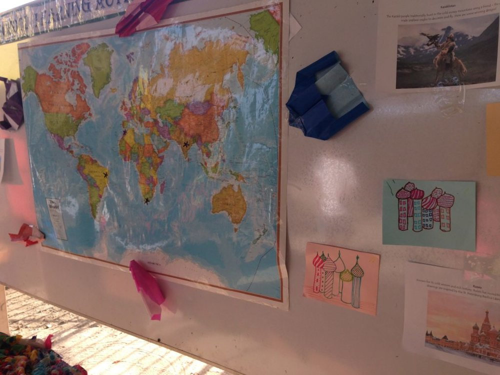 A map was the center of this board, filled with marks of the many places students traveled to this year. Around it, student art is displayed: St. Peter's Basilica from Russia, and paper airplanes representing the companion hunting eagles from Kazakhstan.