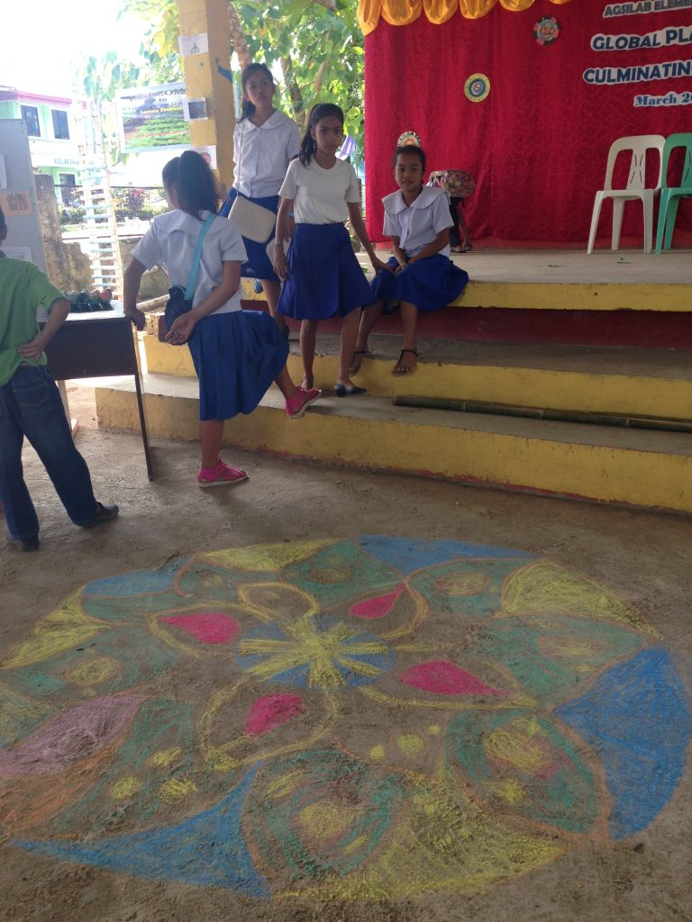 The older class spent time in India and Tibet, where they studied the ancient sacred mandala — a pattern that symbolizes the universe in Buddhism. After a unit on street art in Brazil, students took to heart the idea of spreading art wherever they go– seen in practice here, where several students chose to decorate the floors for the culminating event!