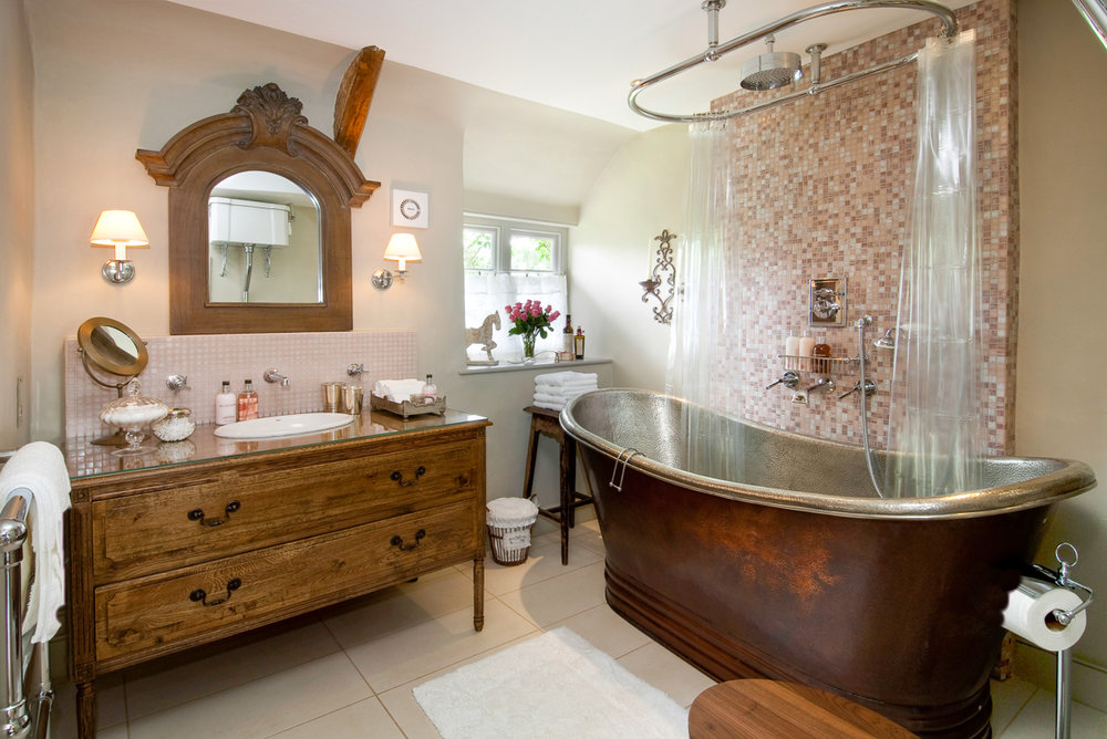 BATHROOM - Upstairs, the cottage's luxury bathroom has a huge vintage copper slipper bath (named by the Evening Standard as one of the UK's best), powerful rainstorm shower, underfloor heating, White Company toiletries, fluffy towels, slippers and cosy dressing gowns.