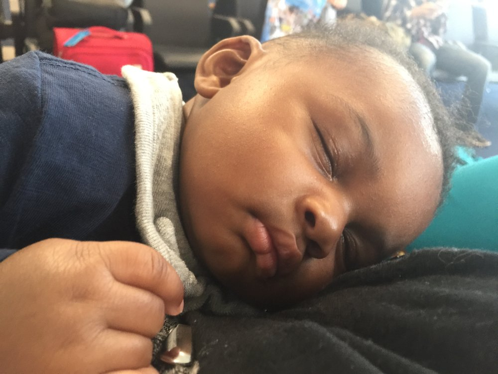 Donovan falls fast asleep in his baby carrier while waiting on airplane repairs with his mother at Hartsfield-Jackson International Airport. LAUREN FLOYD / INFO@HONEYCOMBMOMS.COM