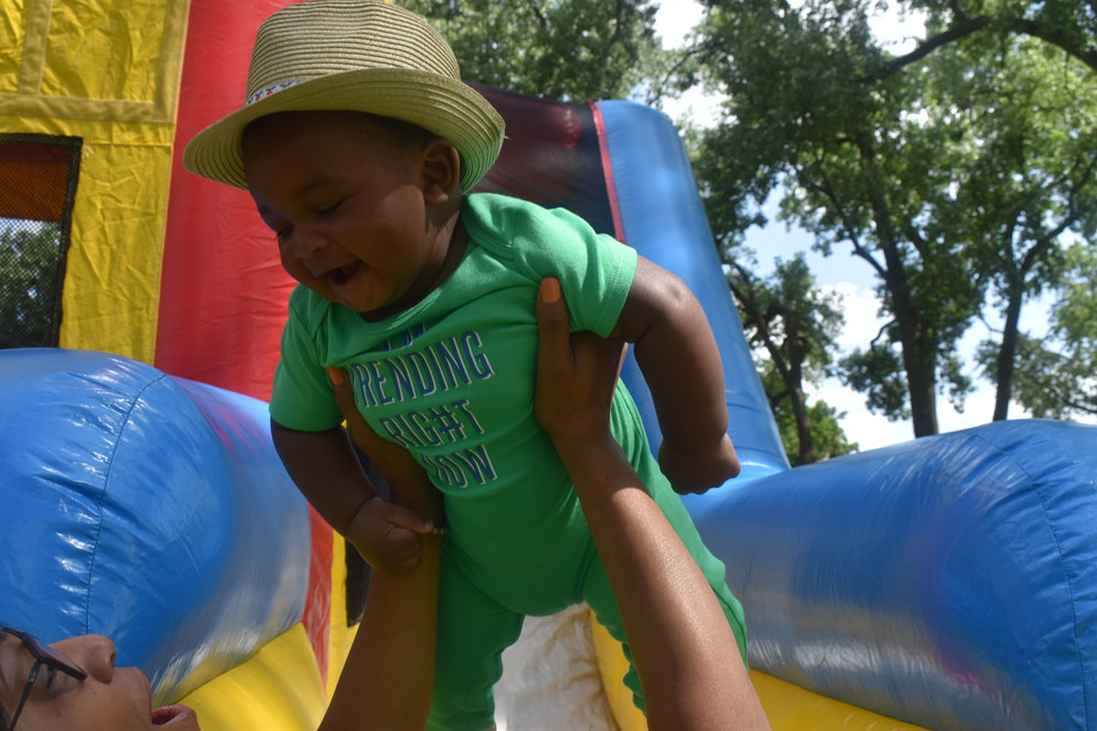 Donovan has some fun with his GiGi, Michelle Breland, at the end of the bouncy house slide. LAUREN FLOYD / INFO@HONEYCOMBMOMS.COM