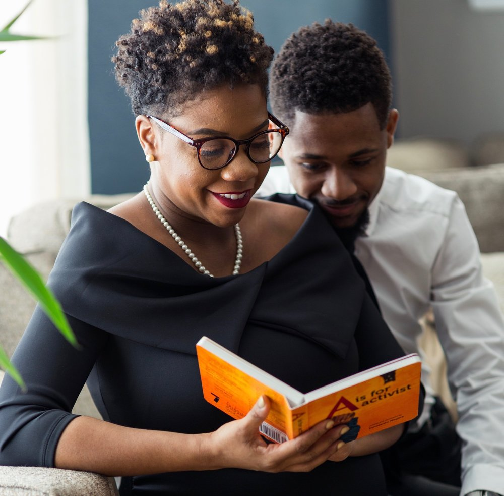 "READ: 14 books for your young, gifted and black child | Honeycomb Moms | Jessica and Corey Hawkins pose for a pregnancy photoshoot with author Innosanto Nagara's ""A is for Activist"". (Credit: Zubayr Mayo)"