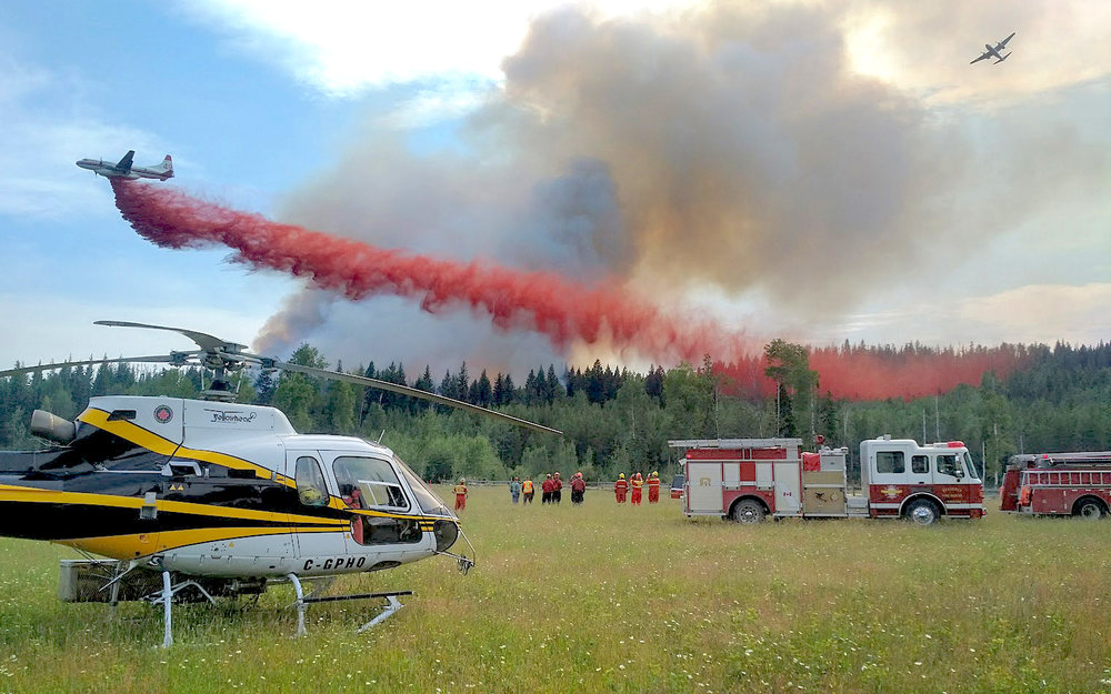 Yellowhead Helicopters airplane letting off red smoke