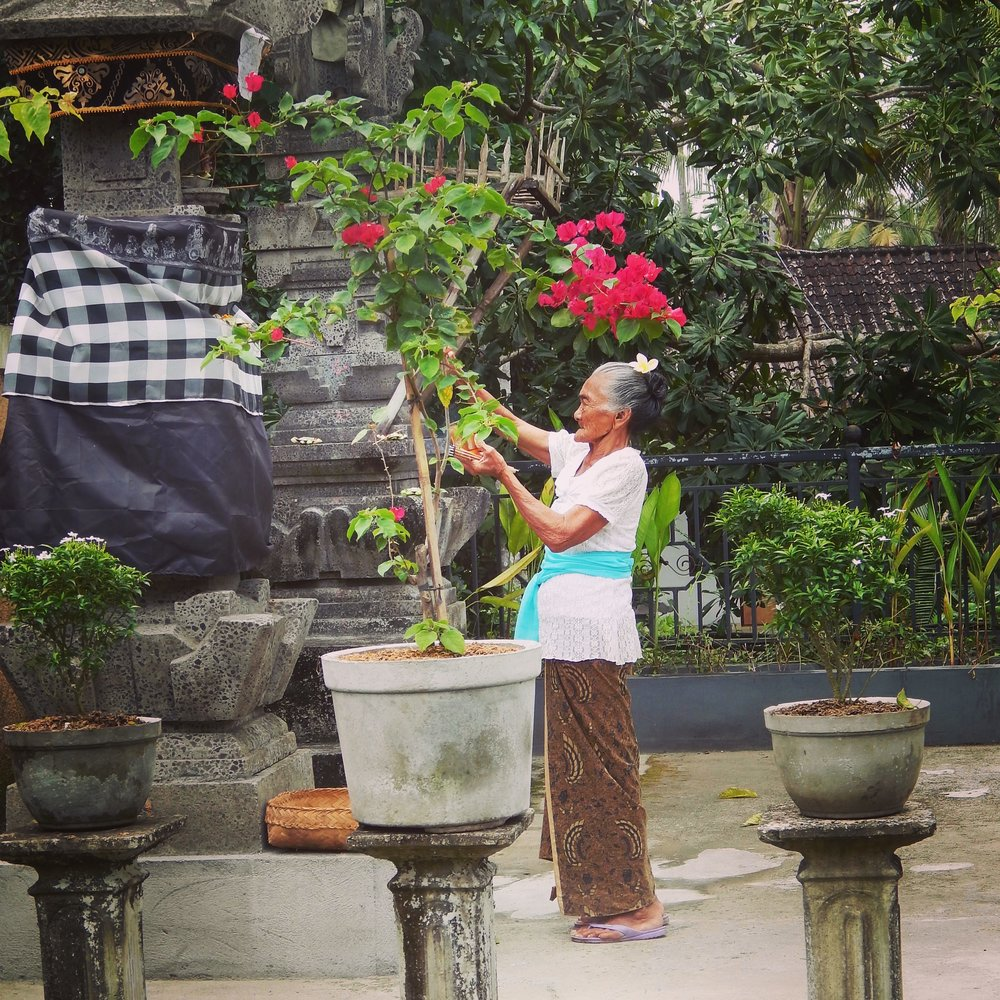 Grandma tending to the offerings at our (her) villa.