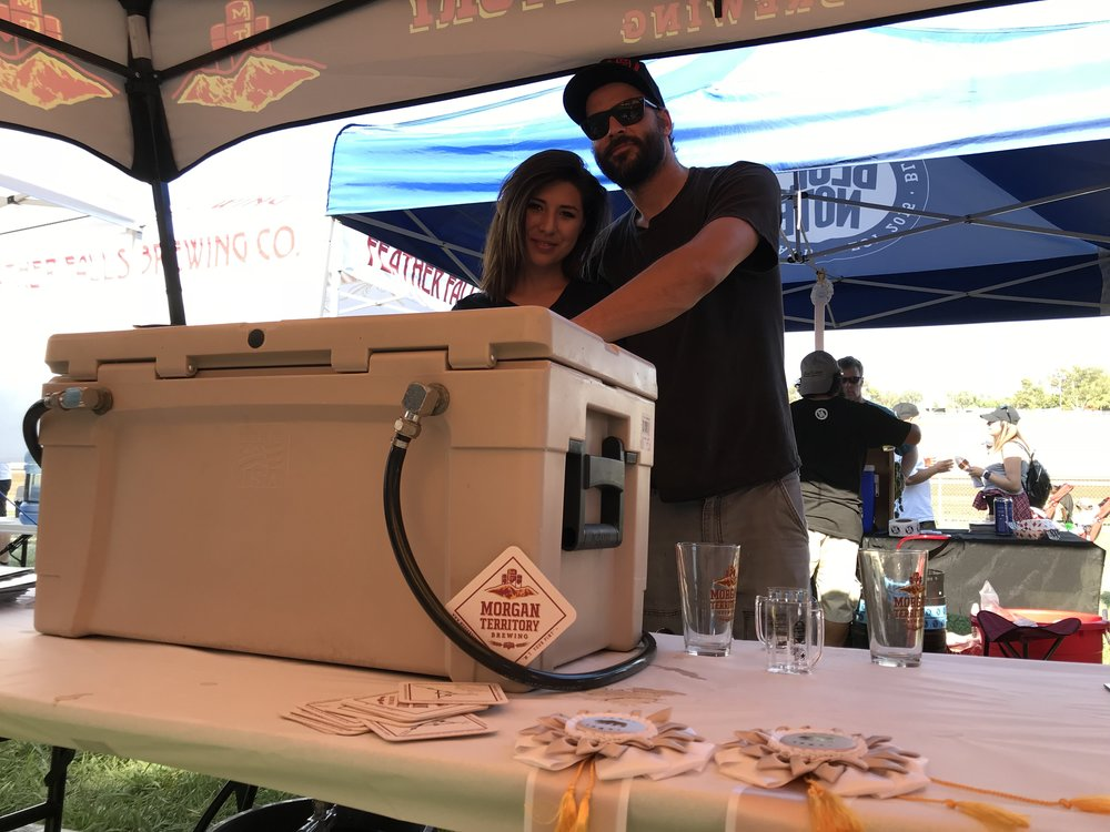 Marlene Heredia and Kyle Manigold empty a mini-keg of award-winning oatmeal stout at the California State Fair brew fest. Photo by Bob Moffitt.