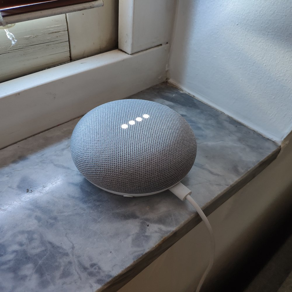 A Google Home mini, situated at the window counter above our couch.