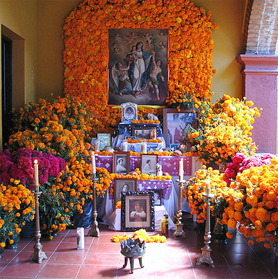 Example of a Day of the Dead altar with marigold flowers and pictures of deceased loved ones