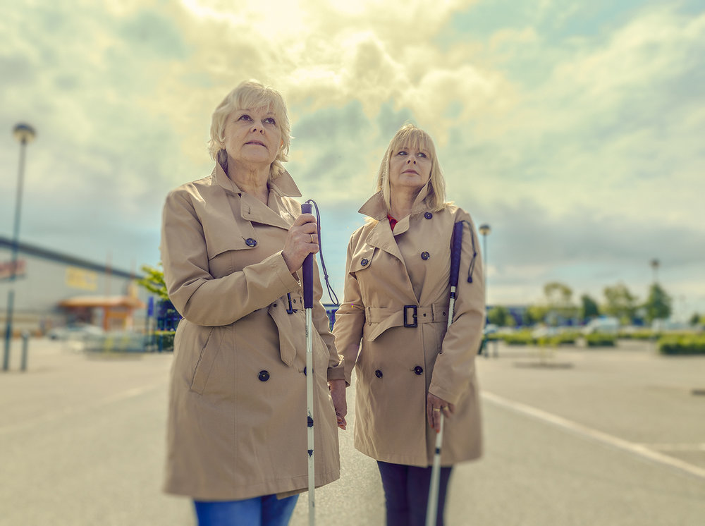 """Carolyn (right) and her elder Sister Elizabeth. This image was taken in a vast empty car park, part-guide and part-experimentation, to signify their learnt knowledge of 'echolocation' which can be best described as spatial representation. """"I use my senses to navigate myself around obstacles that are in my path, it's a skill I've learnt since losing my sight"""". Carolyn tells me how she can also use sound, smell and even the sun to find which direction to move in. 'You become more aware of your surroundings over the years while you adjust to life without sight'. The use of the car park was primarily to get a reaction, I wanted to evoke a little apprehension, my attempt to re-enact or interpret the notion of fiction meeting reality. Elizabeth adds, 'There's no building line, I can't tell where we should walk?' She goes on to say, 'The panic sets in because they are no markers, no sound, there's a heightened sense of isolation and vulnerability, it like shouting at the top of your voice but no-one can hear you'."""