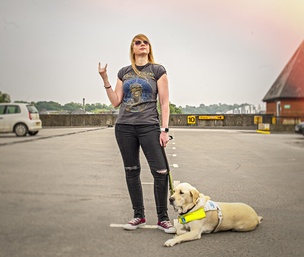 Clare Burham with the guide Dog Saffron, photographed in her local town centre.