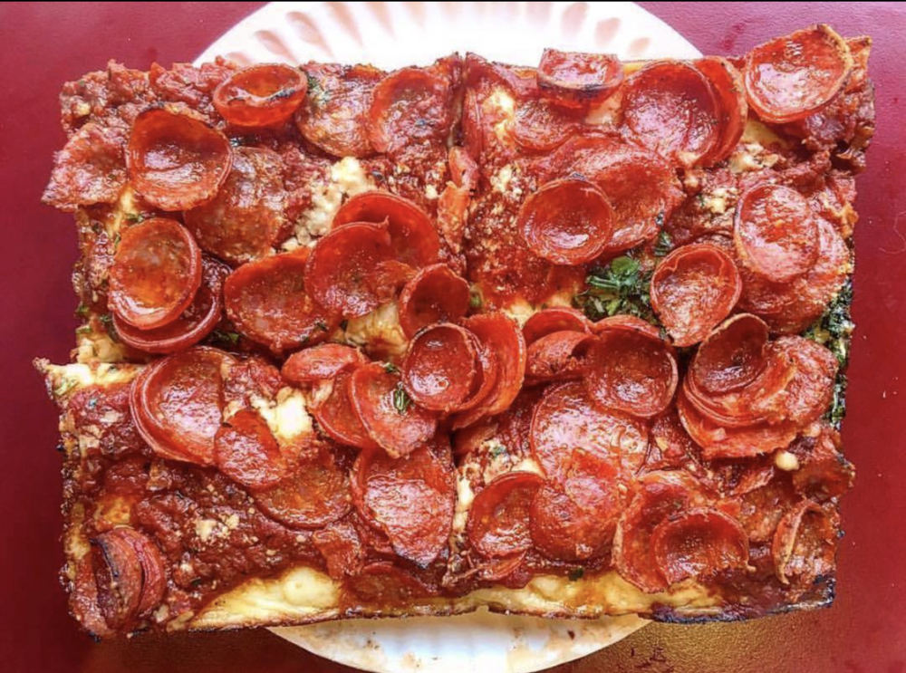 Detroit-Style Pizza - Historians write that Detroit-style pizza dates back to a restaurant called Buddy's Rendezvous, later renamed Buddy's Pizza, in 1946. The story, which is a bit fuzzy, goes that the owner, Gus Guerra, was looking to shake up the menu of his struggling neighborhood bar at 6 Mile and Conant. He came to acquire a few unused blue steel industrial utility trays from a friend who worked at a factory. Seeing the trays, and despite their rectangular shape, Gus thought that they might good Sicilian-style pizza. Turns out he was right. Oiling the trays, Gus found that the dough became soaked through with the oil, which yielded a crispy, crunchy exterior crust and soft and airy interiors. And the cheese bubbled over and became caramelized—all thanks to the trays. Where the dough came from is a bit muddled. Some say Gus' wife, Anna, got the recipe from her Sicilian mother. Others say an old Sicilian guy taught Gus how to make dough. No one knows for sure. What we all can agree on, however, is that Detroit-Style pizza is downright delicious.Traditionally, this style of pizza is served in a rectangle shape—the result of having many an industrial parts trays on hand in Motor City. Indeed, per Gus Guerra's unique and resourceful pizza-baking technique, pizzas in Detroit are baked in a square pan, which is often not a pizza pan but some sort of industrial pan. These industrial pans were at one time was used to hold small parts in factories and are quite heavy—similar, in fact, to cast iron skillets.The crust of a Detroit-style pizza is thick and quite crisp, often the result of being twice-baked in a well-oiled pan. The pizza is baked until it's got a a chewy, medium-well-done consistency and its bottom and edges feature a fried-like and crunch texture. (This is sometimes the result of certain pizzerias that apply melted butter to the crust with a soft brush prior to baking).Detroit-Style pizza is often served topped with goodies such as pepperoni and mushrooms.