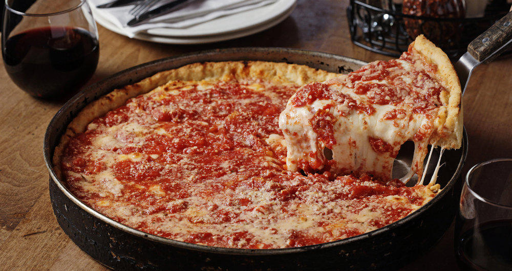 Chicago-Style Deep Dish Pizza - According to Chicago's official cultural historian, Tim Samuelson, there's no one person who is officially credited with having invented Chicago-Style deep dish pizza. It is said the recipe was first conceived at Pizzeria Uno in 1945 by its founder, Ike Sewell. Others say that it was Uno's aforementioned pizza chef, Rudy Malnati, Sr., who created it.History aside, what makes deep dish unique is—as its name certainly implies—is its deep (or high-edged) crust, which when filled with pizza ingredients such as chunky tomato sauce and copious amounts of melty, gooey cheese, begins to resemble more of a pie, or even a stuffed pizza, far more so than it resembles a flatbread (of Neapolitan fame). While the pie might appear to be a pure gut bomb (and don't confuse what we're saying, because it totally is), the crust itself is actually of only thin to medium thickness.Deep dish Chi-Town pizza is characteristically round as it is baked in a round, steel pan similar to one you might use to bake a cake or a pie. (Think springform pans). The pan is well oiled (à la Detroit style), which helps make the pizza easy to remove and which also gives the outside of the crust a fried effect.When you take a bite of a good deep dish pizza, you may notice that the crust tastes a bit sweet. That's because in addition to using a run-of-the-mill (see what we did there?) wheat flour, some pizzerias use corn meal or semolina, which provide a sweeter—and more yellowish in color/tone—flavored crust.Another noteworthy characteristic of Chicago-Style deep dish pizza is that it usually appears upside down. Rather than having the sauce atop the dough, and then the cheese and toppings, deep dish is made with the cheese (often sliced mozz) melted onto the crust first. The cheese is then covered with toppings, such as pepperoni or sausage (which forms a nice patty-like layer) or veggies such as peppers, onions and mushrooms. Then comes the sauce, which is uncooked and is often made from canned, crushed tomatoes (which gives it a nice chunky texture) and sometimes a sprinkling of parmesan cheese.FANGATING™ TIP: If you're getting your deep dish to go, ask them not to slice it for you. If you slice it, moisture from the sauce and the toppings will seep into the crust and the pie will take on a soggy texture. What a sad, sad thing to behold.