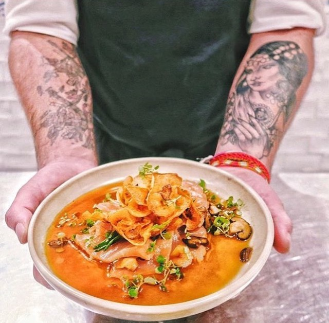 Alejandro's artistically tattooed arms presenting one of his dishes