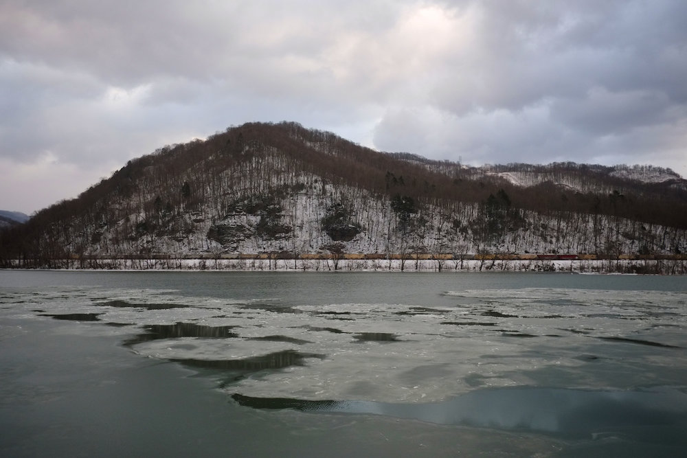 Roger May . January 25, 2014. Coal-laden railcars roll through the upper Kanawha Valley along the icy Kanawha River, just west of the confluence of the New and Gauley Rivers at Glen Ferris, Fayette County, West Virginia. (First published in The Guardian on January 30, 2014.)