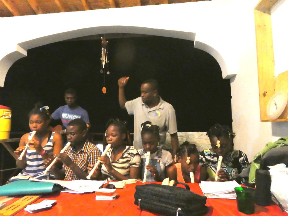 Feed My Lambs Students in Haiti playing their newly donated recorders under the direction of Mr. Kelly.