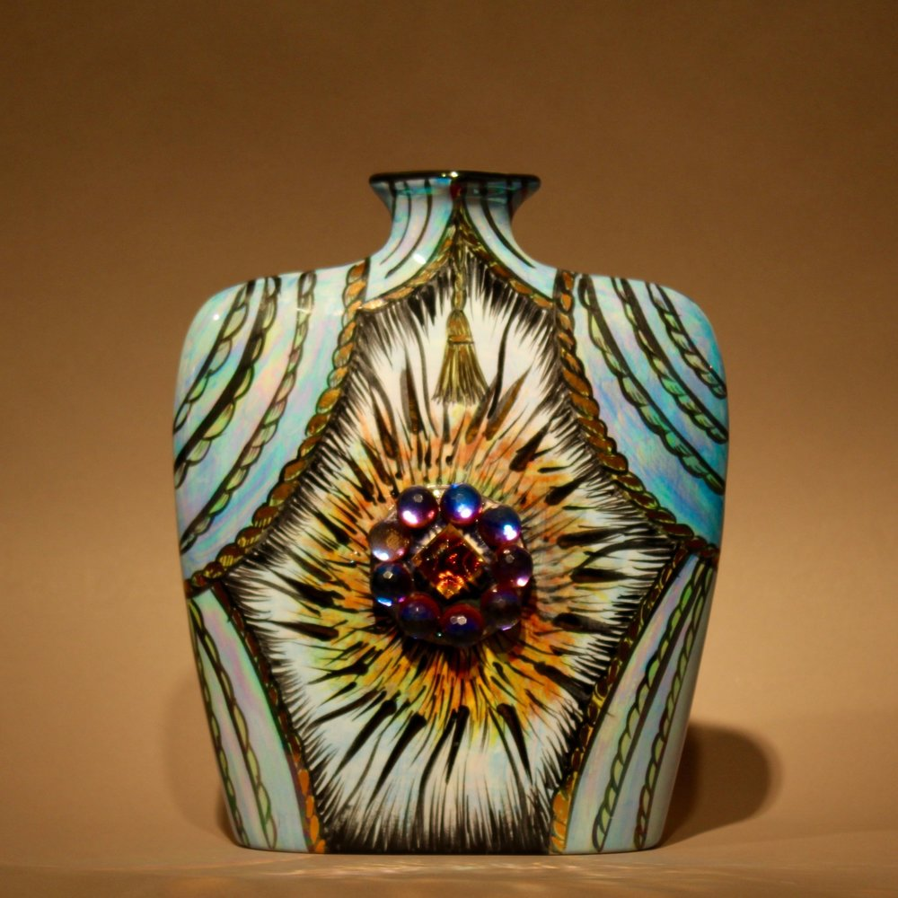 """Dimensions: 9"""" H  Year: 2014  Medium: Gold and luster overglaze on low fire ceramic vase embellished with Helio Green and blue German Crystal medallion  Price: $950"""