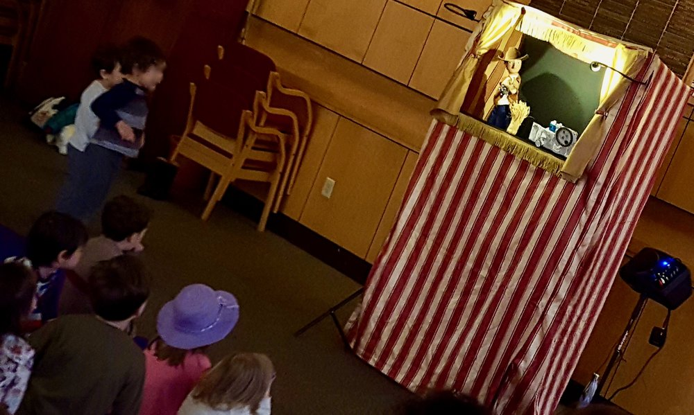 "Jenny from WonderSpark presented ""The Wild West Mystery,"" and kids sang along, got clues, and helped solve the mystery! Afterwards, kids made paper-bag puppets to take home. March 2018."