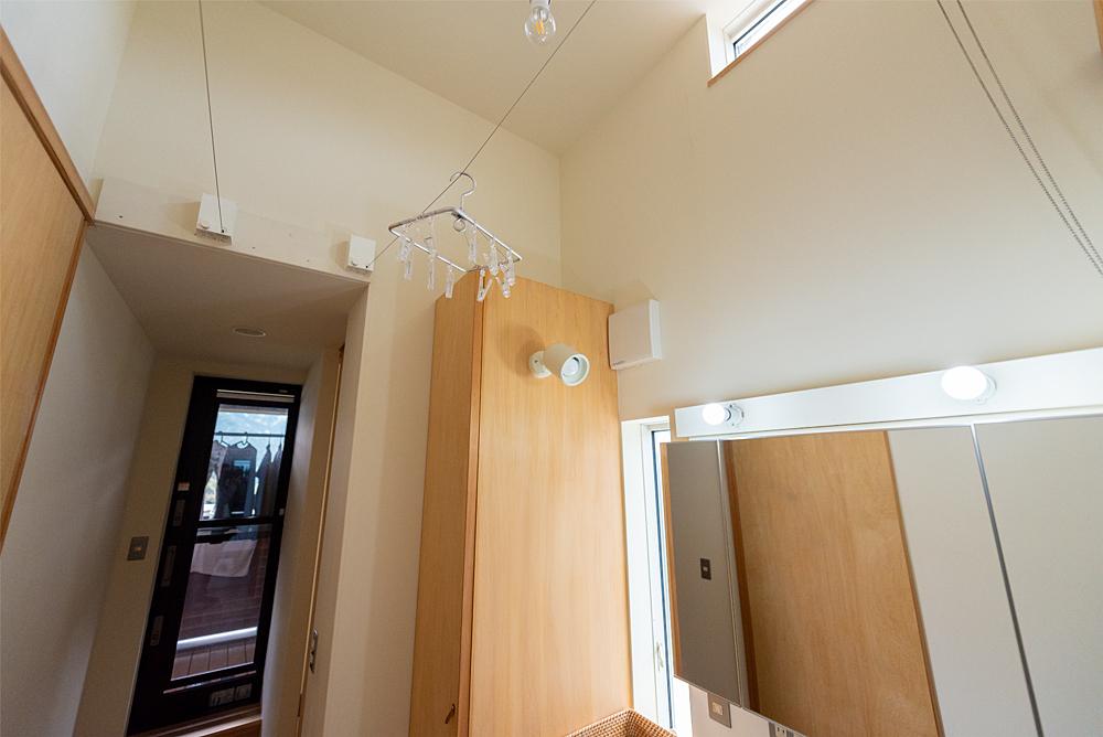 掃除機に合わせた専用収納。洗濯物干しのワイヤーと洗面台ライトはDIYによるもの。