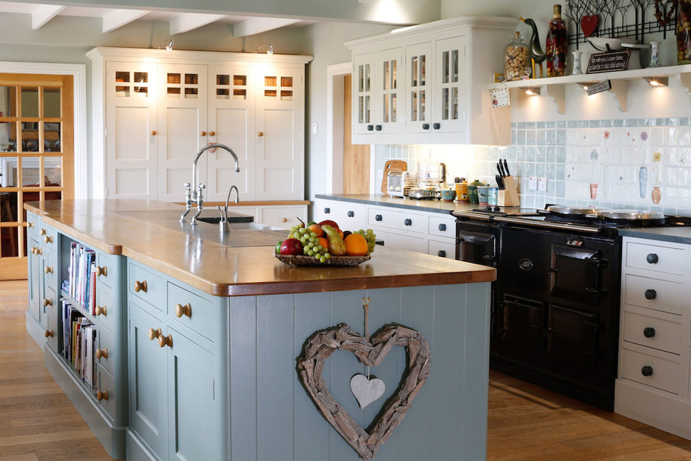 """We love the fact that it's a place the children enjoy coming back to."" - This handmade kitchen was hand built seven years ago, and it has stood the test of time. On this project we also fitted ceiling beams for a 'country cottage' feel, using soft Farrow & Ball colours to make the most of the wonderful light."