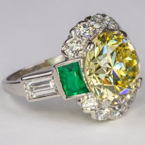 A Fancy Yellow Diamond, Emerald and Platinum Ring sold for $55,000