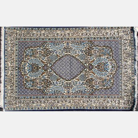 PERSIAN SILK AND WOOL RUG   Having a floral center medallion on an all over floral decorated field   Estimate: $100 - $200