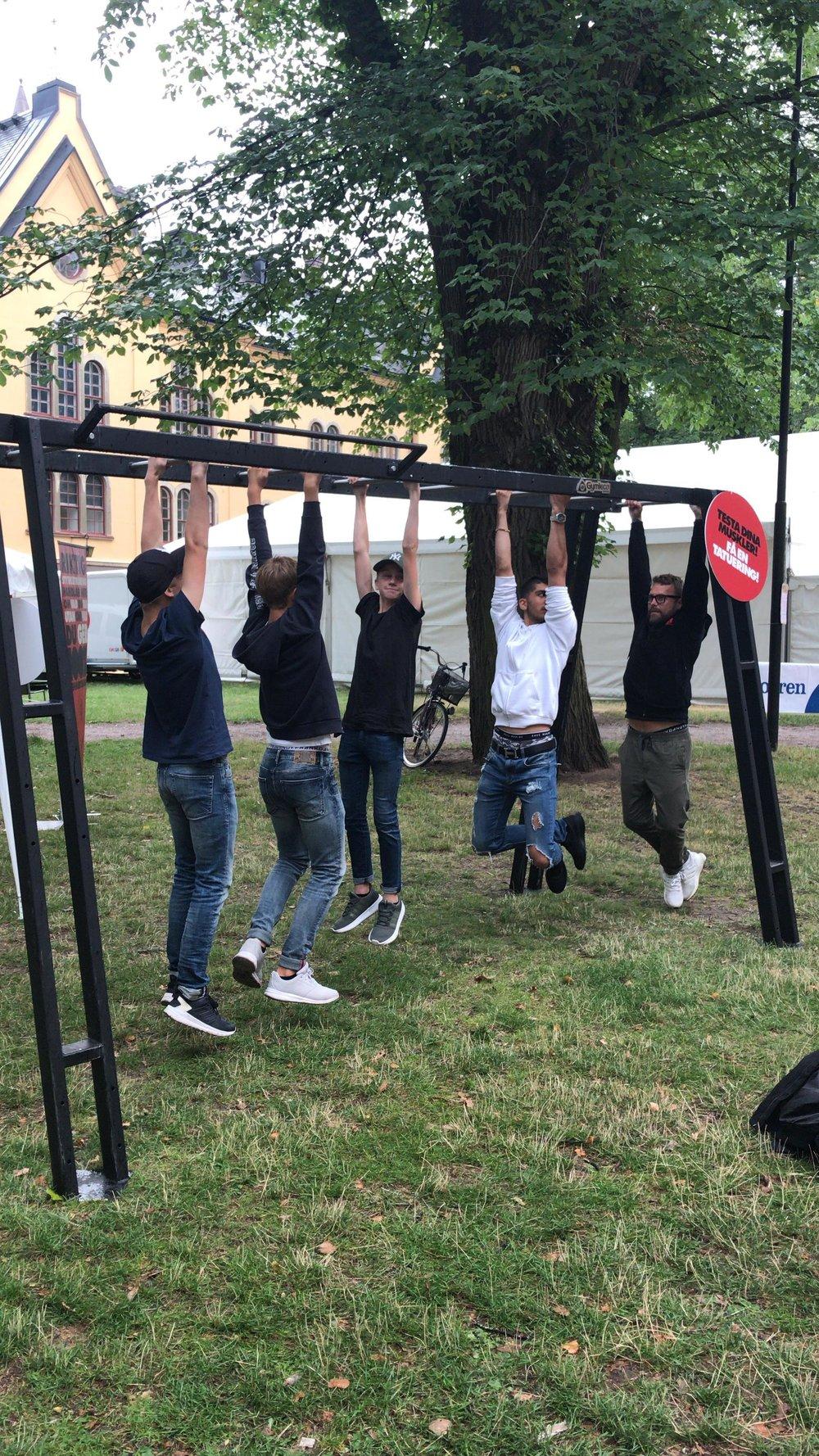 """""""Häng-tävlingen"""" är lika klassisk som krävande. Här utmanas 100% Ren Hårdtränings projektledare Johan Öhman (till höger)av ett gäng lokala förmågor. Sannolikt var projektledaren chanslös, trots misstänkt markkontakt."""