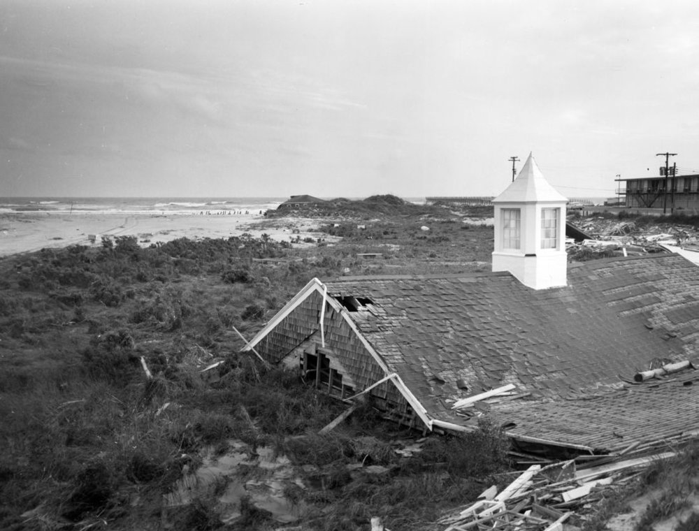 "Hurricane Donna, September 11-12, 1960. The roof of the Dunes Club at Atlantic Beach is seen in foreground. Back is captioned, ""Dunes Club, Atlantic Beach"". From Carolina Power and Light (CP&L) Photograph Collection (PhC.68), North Carolina State Archives."