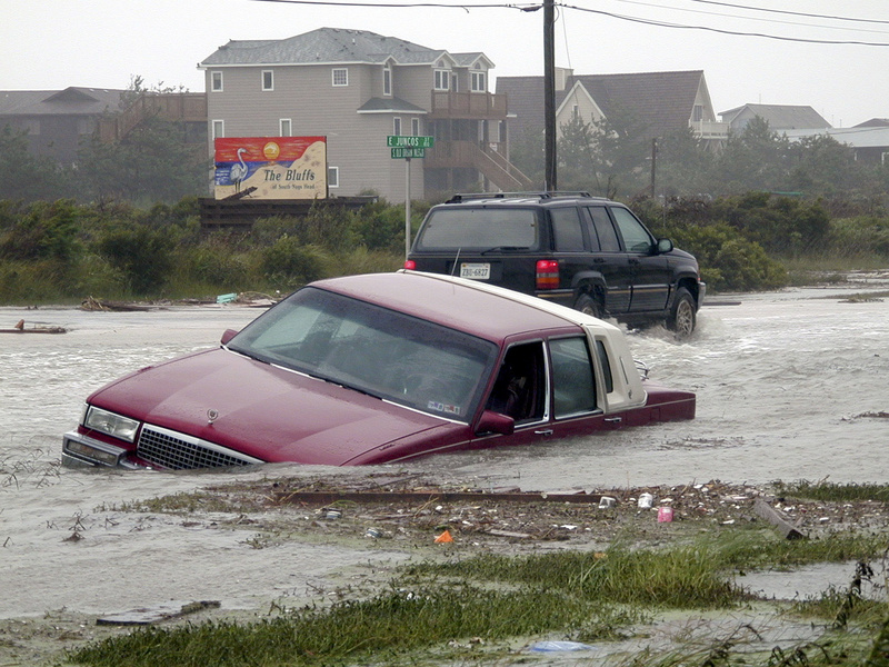 Photo date: September 1, 1999 Photographer: FEMA / Dave Gatley Photo location: Nags Head NC Categories: Hurricane/Tropical Storm   Here a car lays flooded out along Old Oregon Inlet Road as the rains and ocean overwash flooded out stretches of the coastal highway. Fifty-plus miles of Highway 12, which leads South from Nags Head to Cape Hatteras and the Hatteras Island, was closed off to traffic due to the sand drifts that covered the coastal highway from ocean overwashes. The change of direction by Dennis brought high seas and winds that battered and flooded the coastal road. Photo by DAVE GATLEY/FEMA News Photo    Read more:  http://www.city-data.com/disaster-photos/1632.html#ixzz5GnfUnoGA